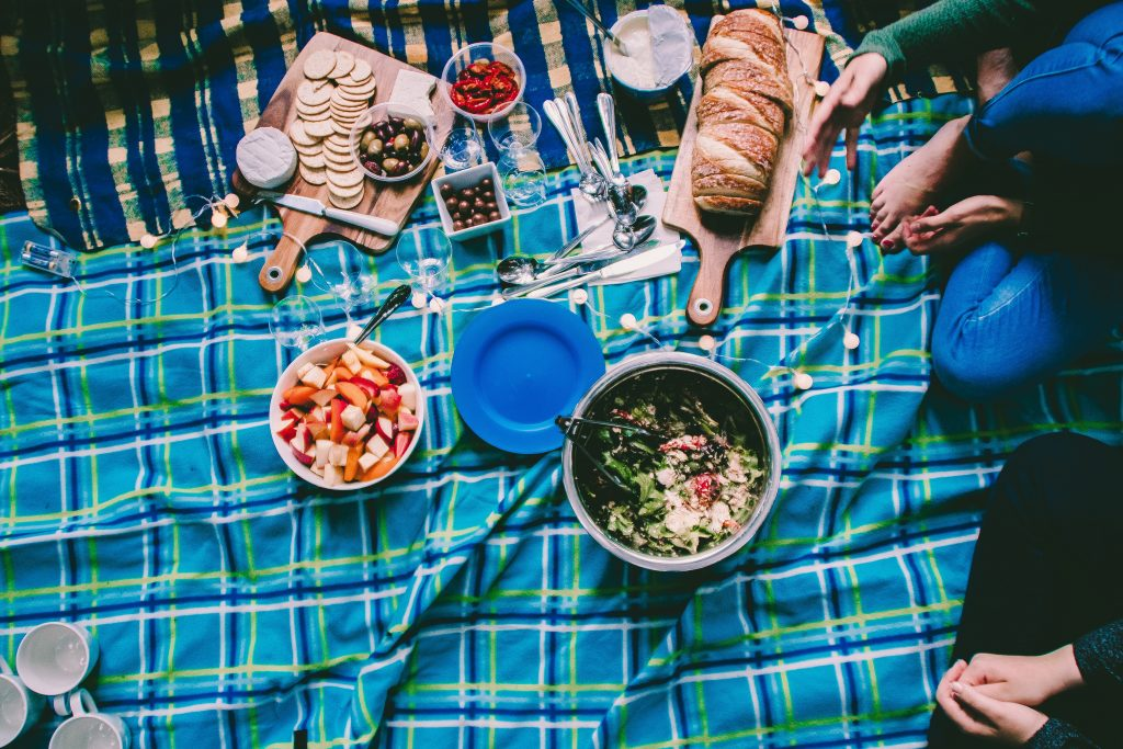 Picnic food with bread, salad, and cheese and reusable picnicware.
