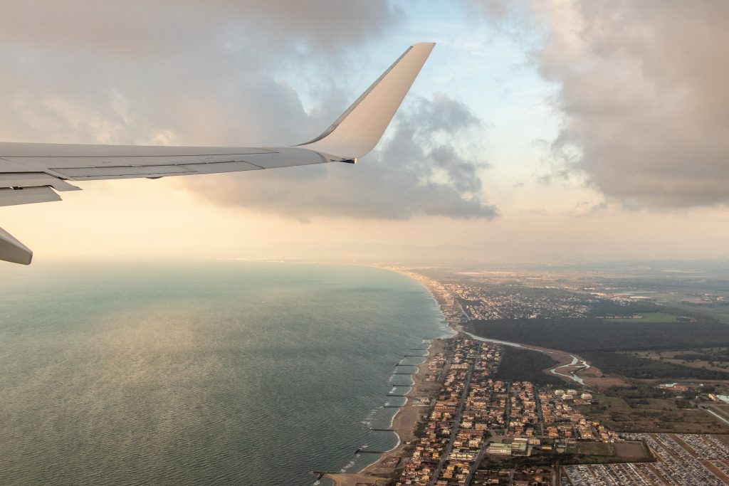 Airplane wing pictured from inside the plane above a coastal city