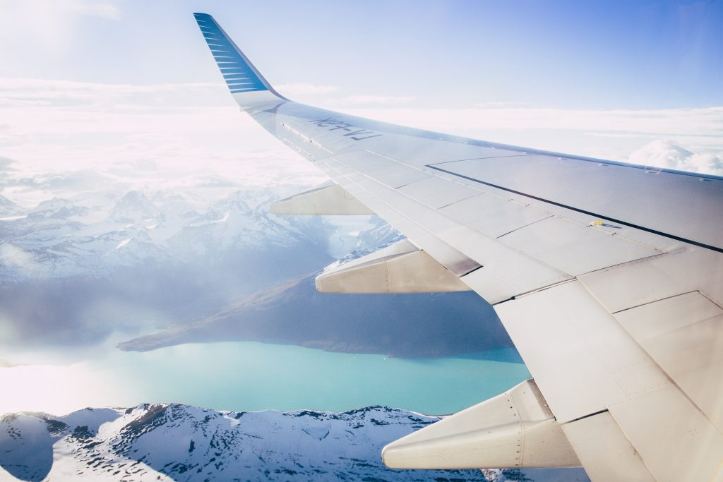 Airplane wing pictured from inside the plane over mountainous landscape